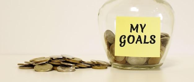 Barattolo di vetro con monete per il risparmio. l'iscrizione sulla nota carta i miei obiettivi. concetto finanziario.