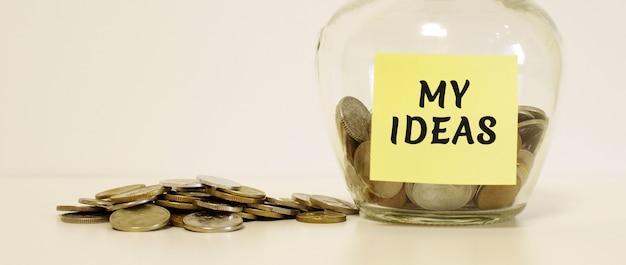 Barattolo di vetro con monete per il risparmio. l'iscrizione sulla nota carta le mie idee. concetto finanziario.