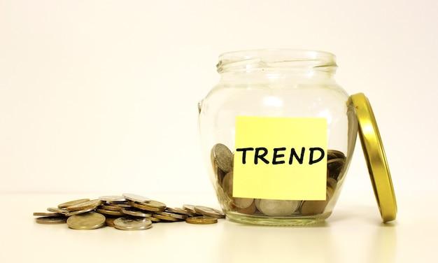 Barattolo di vetro con monete per il risparmio l'iscrizione sul foglio di carta trend