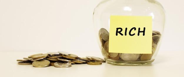 Barattolo di vetro con monete per il risparmio. l'iscrizione rich sulla nota carta. concetto finanziario.
