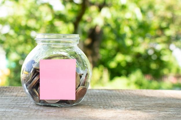 Un barattolo di vetro con monete su un tavolo di legno. budget per investire.