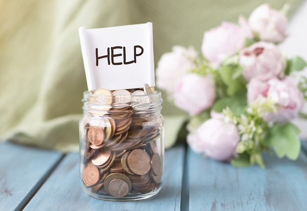 Vaso di vetro con monete sulla tavola di legno. concetto di donazioni