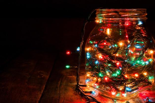 Vaso di vetro con ghirlande su sfondo nero e spazio per il testo
