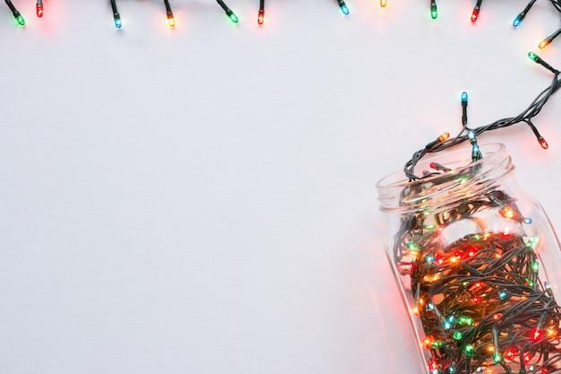 Vaso di vetro con una vista superiore del bordo ghirlanda luminosa su uno sfondo bianco