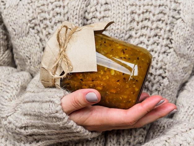 Vaso di vetro con marmellata di uva spina nelle mani di una ragazza