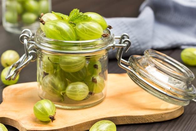 Barattolo di vetro con uva spina verde a bordo. tovagliolo grigio. fondo in legno scuro. vista dall'alto