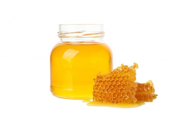 Vaso di vetro con miele e favi isolati su sfondo bianco