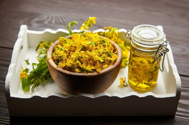 Vaso di vetro con estratto di olio di iperico o iperico e ciotola di legno con fiori freschi su vassoio di legno bianco