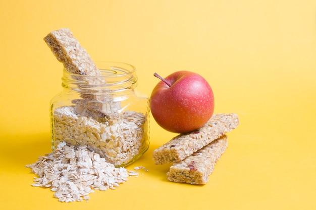 Barattolo di vetro con farina d'avena, una mela e diverse barrette proteiche per uno spuntino su una superficie gialla