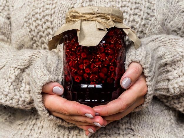 Vaso di vetro con marmellata di lamponi nelle mani delle ragazze