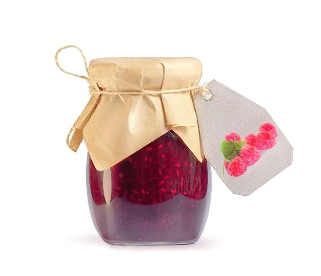Vaso di vetro con marmellata di lamponi su bianco