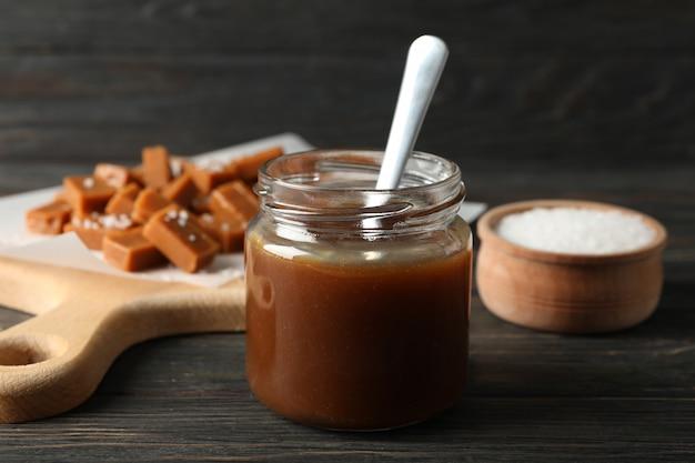 Vaso di vetro con caramello salato e caramelle su spazio in legno, spazio per il testo