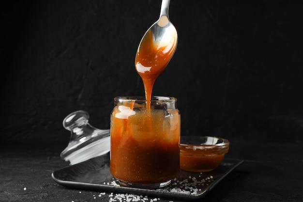 Vaso di vetro con caramello salato e cucchiaio su spazio nero, copia spazio