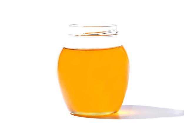 Vaso di vetro con miele dolce isolato su sfondo bianco.