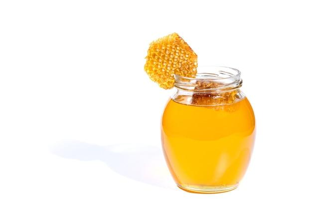 Vaso di vetro con miele dolce isolato su superficie bianca.