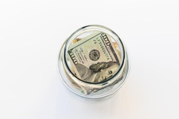 Vaso di vetro con contanti statunitensi, 100 dollari su sfondo bianco, vista dall'alto, piatto. soldi e finanza.