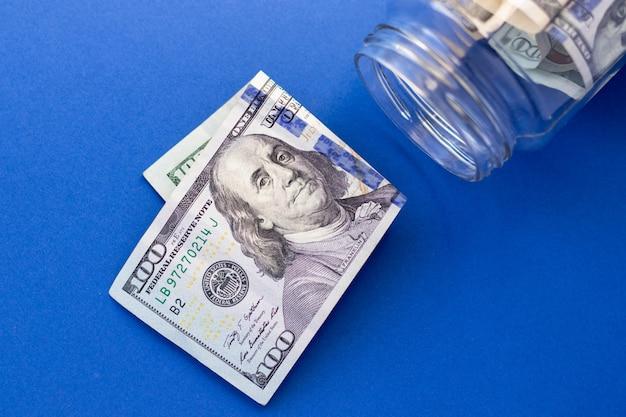 Vaso di vetro con contanti statunitensi e 100 dollari su sfondo blu, vista dall'alto, piatto. soldi e finanza.