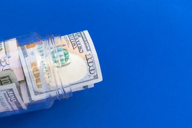 Barattolo di vetro con contanti statunitensi, 100 centinaia di dollari su sfondo blu, vista dall'alto, piatto. soldi e finanza.