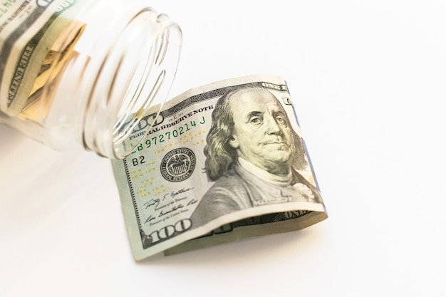 Vaso di vetro con contanti statunitensi e 100 dollari su sfondo bianco, vista dall'alto, piatto. soldi e finanza.