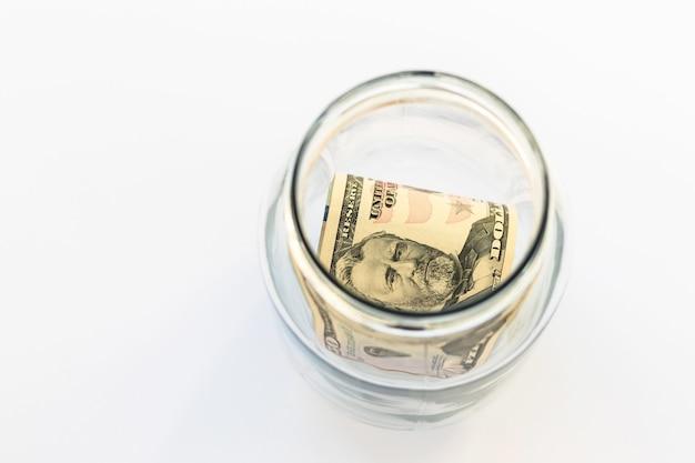 Vaso di vetro con contanti usa, 50 dollari su sfondo bianco, vista dall'alto, piatto. soldi e finanza.