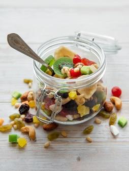 Vaso di vetro con vari tipi di frutta secca e noci su una superficie di legno