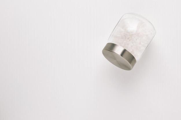 Vaso di vetro con sale bianco su sfondo bianco