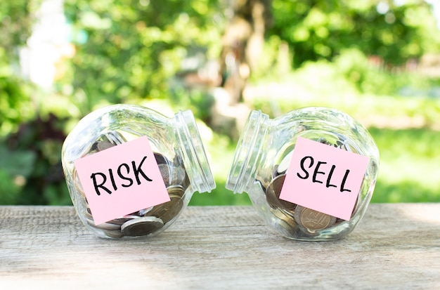 Barattoli di vetro con monete e le scritte risk e sell stanno su un tavolo di legno. bilancio di investimento.