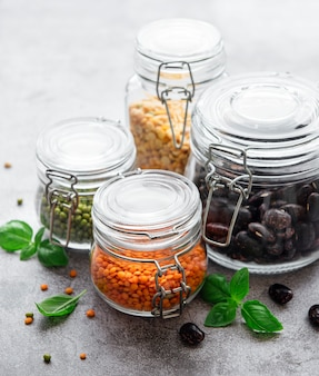 Barattoli di vetro con diversi tipi di legumi su una superficie di cemento grigio