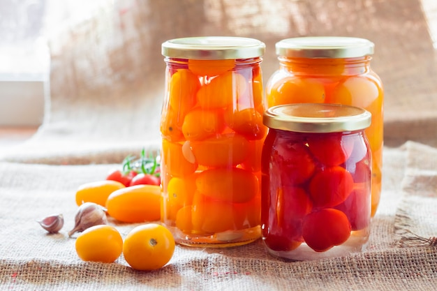 Barattoli di vetro con pomodori marinati rossi e gialli fatti in casa, sigillati con coperchio in metallo