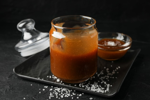 Barattoli di vetro con caramello salato su spazio nero, fine in su