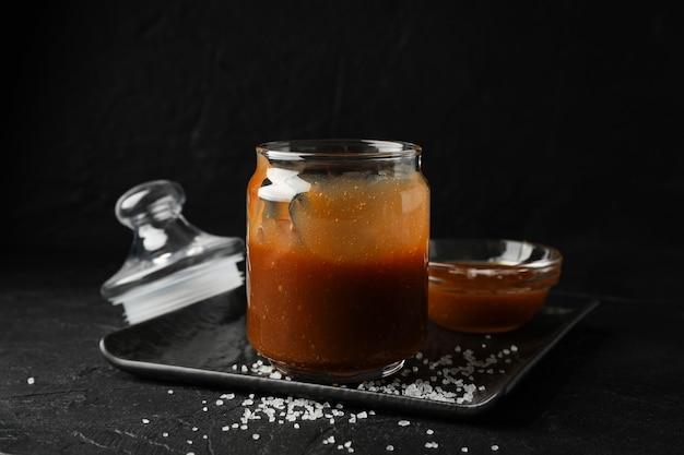 Vasetti di vetro con caramello salato su spazio nero, spazio per il testo