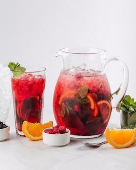 Bicchiere e brocca di limonata fresca a bacca rossa con menta arancia e ghiaccio