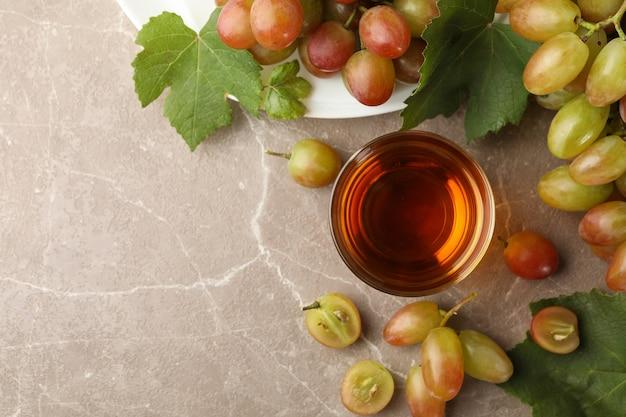 Bicchiere di succo e piatto con uva sul grigio
