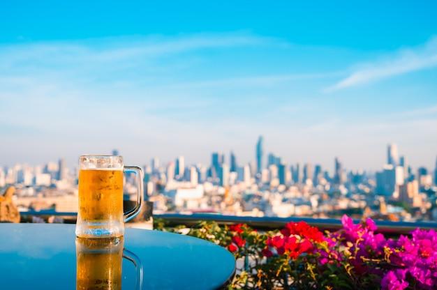 Bicchiere di birra chiara sul tavolo con vista di paesaggio urbano di edifici grattacielo di bangkok in background, thailandia