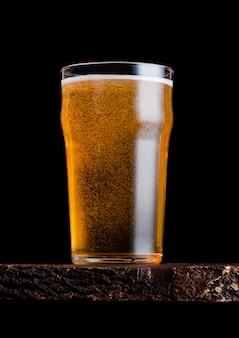 Vetro della birra chiara con schiuma e bolle sul bordo di legno d'annata