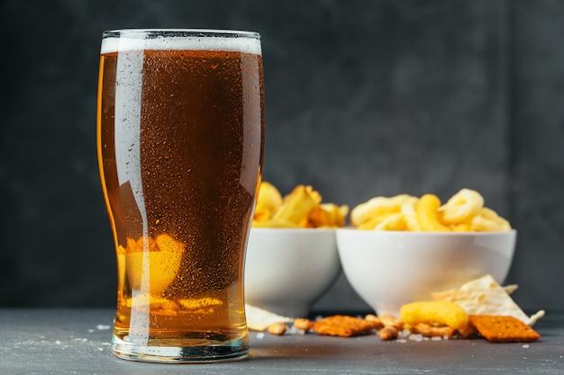 Vetro della birra chiara con le ciotole dello spuntino sulla pietra scura