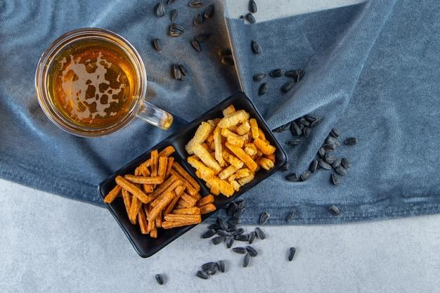 Bicchiere di birra chiara con ciotole snack su asciugamano, sulla superficie di marmo.