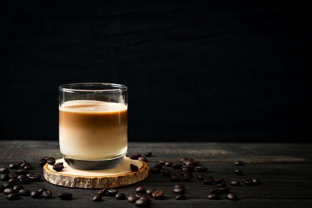 Bicchiere di caffè latte, caffè con latte sul tavolo di legno