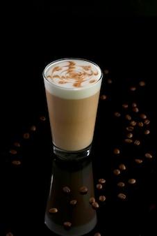 Vetro del caffè del latte con i fagioli su fondo nero
