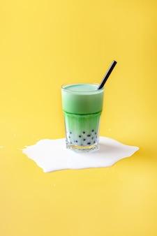 Un bicchiere di latte con tè matcha con palline di tapioca e latte versato