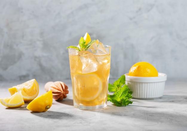 Bicchiere di tè freddo al limone su sfondo grigio cemento con menta e ghiaccio