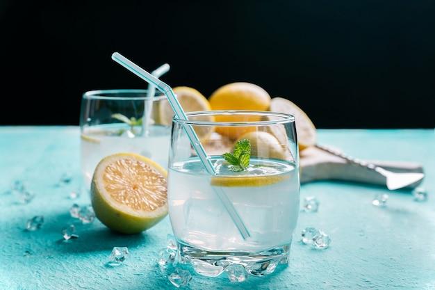Bicchiere di limonata accanto ai limoni, blu