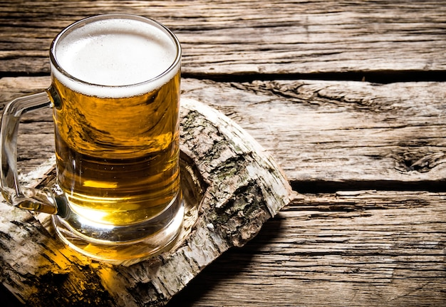 Bicchiere di birra chiara su un piedistallo di betulla. su un tavolo di legno.