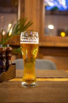 Bicchiere di birra chiara su un pub scuro, soft focus