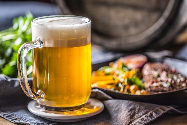 Bicchiere di birra leggera in pub o ristorante sul tavolo con cibo delizioso.