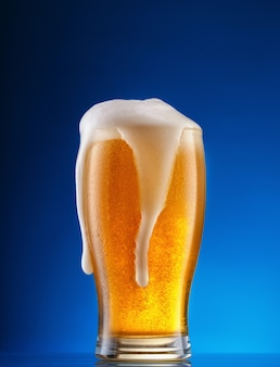 Bicchiere di birra leggera con schiuma a goccia sul blu