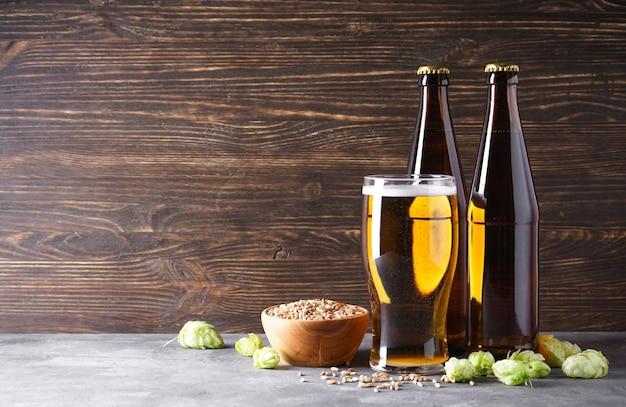 Bicchiere di birra chiara con due bottiglie su un tavolo di cemento