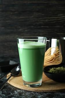 Bicchiere di latte matcha e accessori per fare sul tavolo affumicato nero