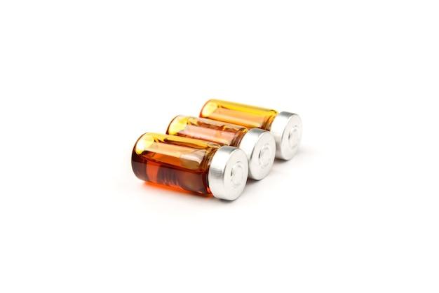 Fiala medica di vetro con la capsula e l'olio all'interno isolato su bianco