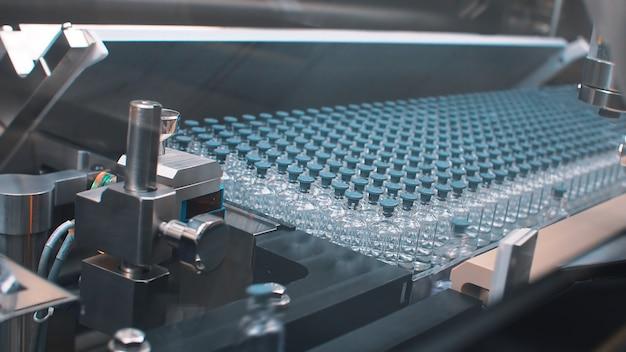 Bottiglie mediche di vetro nella produzione farmaceutica per la produzione di vaccini e prodotti medici. coronavirus